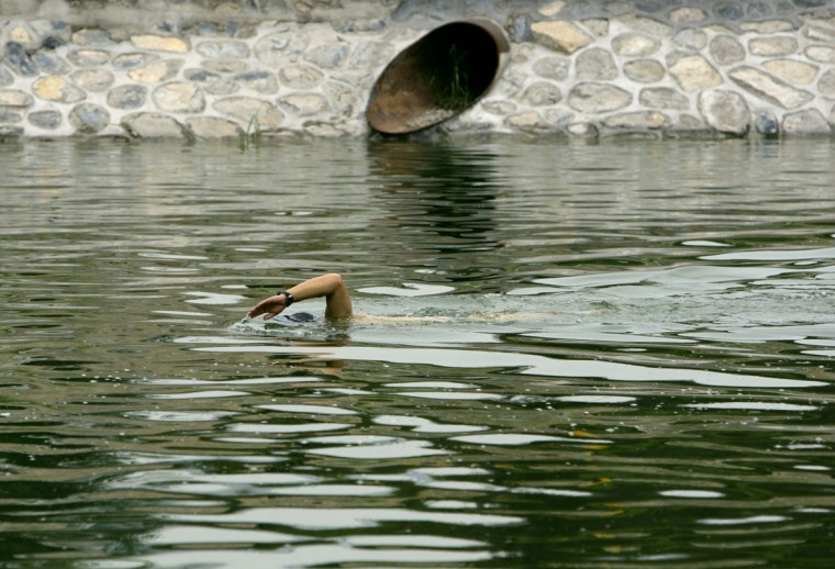 A man swims in a polluted canal in the centre of Beijing on August 16, 2007. (REUTERS/David Gray)