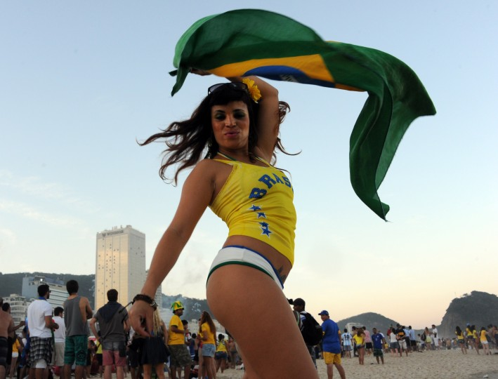 A Brazilian woman waves a flag at the Fan Fest in Copacabana beach in Rio de Janeiro, Brazil during the 2014 FIFA World Cup Brazil vs Colombia match. (Tasso Marcelo/AFP-Getty Images)