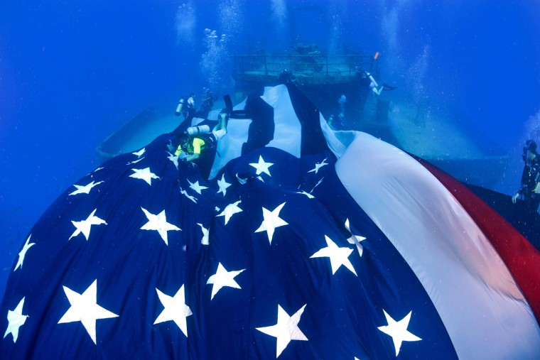 Divers deploy a large American flag on the USNS General Hoyt S. Vandenberg, a former military troop transport and missile-tracking ship scuttled more than five years ago in the Florida Keys National Marine Sanctuary as an artificial reef off Key West, Florida. The flag formerly flew at a Morris, Illinois, memorial park for the September 11, 2001, New York City terrorists' attack victims. The flag was to be retired after being badly tattered by the weather, but Morris attorney Scott Belt conceived the idea of mending the flag and unfurling it on the Vandenberg. (Scott Belt/Florida Keys News Bureau/ via Reuters)