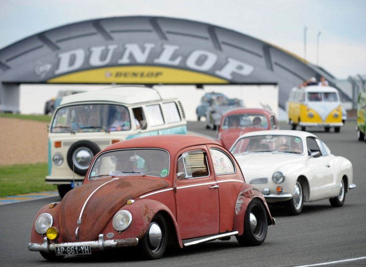 """People parade with their Volkswagens during the """"Super VW Festival"""" on Le Mans' circuit, western France. The festival, which runs from July 25 to 27, gathers nearly 1200 aircooled Volkswagen cars including the models Beetle, Transporter, and Dune Buggy. (Jean-Francois Monier/AFP-Getty Images)"""