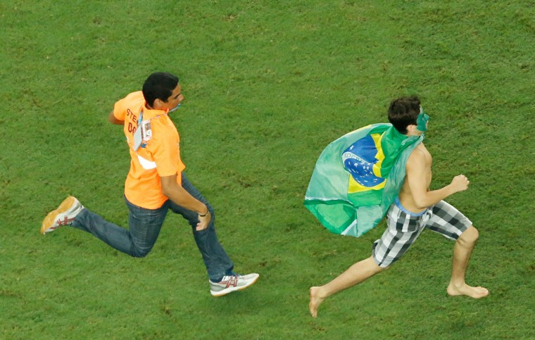 A steward runs after a Brazilian fan who invaded the pitch at the end of the quarter-final football match between Brazil and Colombia at the Castelao Stadium in Fortaleza during the 2014 FIFA World Cup. (Fabrizio Bensch/Pool/AFP-Getty Images)