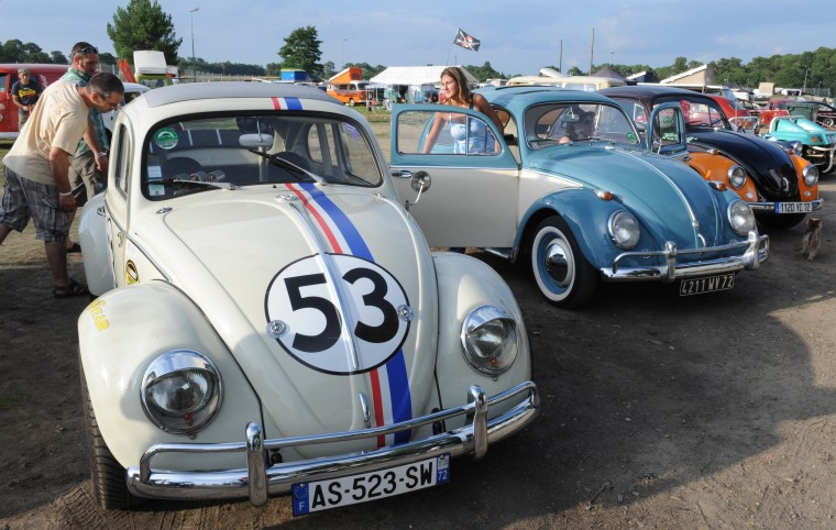 """People look at Volkswagen Beetles displayed during the """"Super VW Festival"""" on Le Mans' circuit, western France. The festival, which runs from July 25 to 27, gathers nearly 1200 aircooled Volkswagen cars including the models Beetle, Transporter, and Dune Buggy. (Jean-Francois Monier/AFP-Getty Images)"""