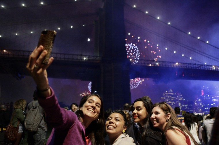 People take pictures of themselves as the annual fourth of July fireworks show goes off in background over the East River in Brooklyn. The fireworks show returned to the East River for the first time since 2008. The United States marks 238 years as an independent nation as it celebrates the national holiday. (Kena Betancur/Getty Images)