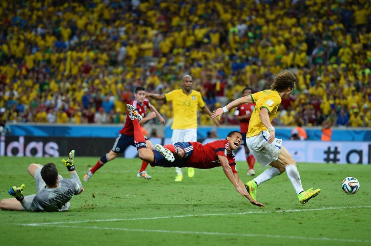 Julio Cesar of Brazil challenges Carlos Bacca of Colombia resulting in a penalty kick and yellow card for Julio Cesar as David Luiz defends during the 2014 FIFA World Cup Brazil Quarter Final match between Brazil and Colombia at Castelao in Fortaleza, Brazil. (Jamie McDonald/Getty Images)