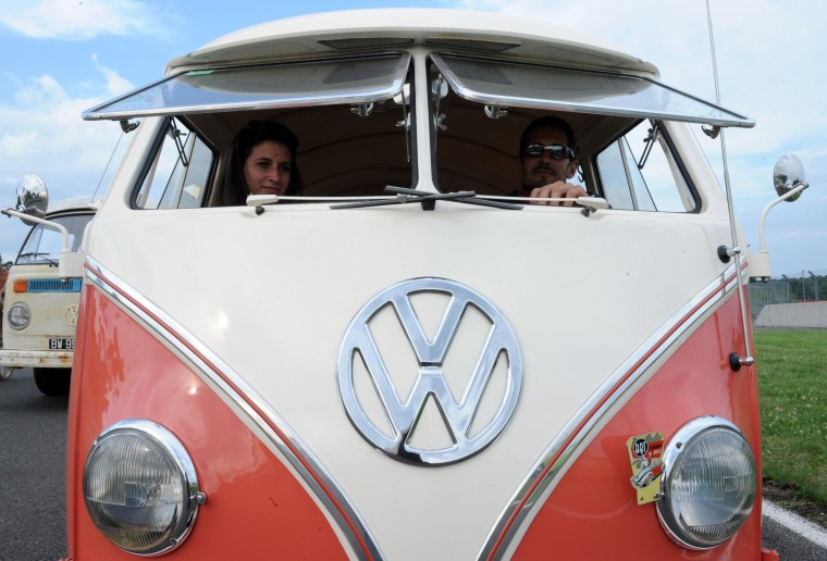 """French collector Sylvain Perdoux sits in his Volkswagen Transporter during a Volkswagen parade during the """"Super VW Festival"""" on Le Mans' circuit, western France. The festival, which runs from July 25 to 27, gathers nearly 1200 aircooled Volkswagen cars including the models Beetle, Transporter, and Dune Buggy. (Jean-Francois Monier/AFP-Getty Images)"""