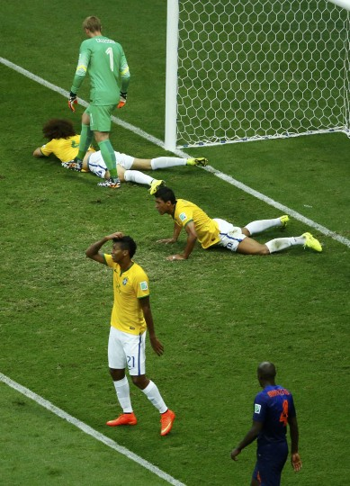 Brazil's David Luiz (top L) and Paulinho (R) react on the ground after missing an opportunity to score a goal during their 2014 World Cup third-place playoff against the Netherlands at the Brasilia national stadium in Brasilia. (Ruben Sprich/Reuters)