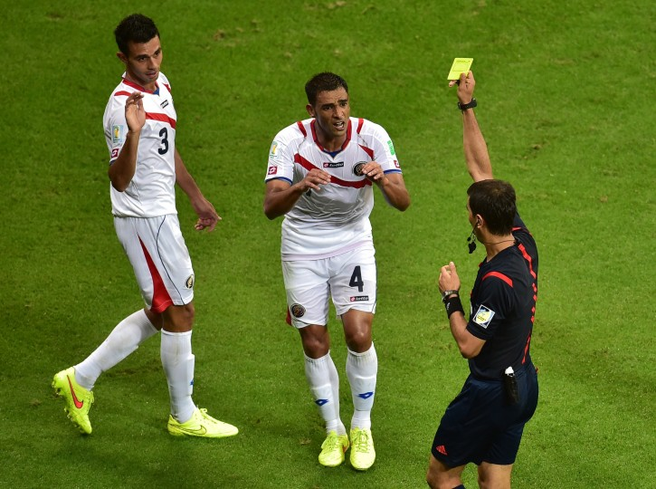 Costa Rica's defender Michael Umana (C) receives a yellow card by Uzbek referee Ravshan Irmatov (R) during a quarter-final football match between Netherlands and Costa Rica at the Fonte Nova Arena in Salvador during the 2014 FIFA World Cup. (Gabriel Buoys/AFP-Getty Images)