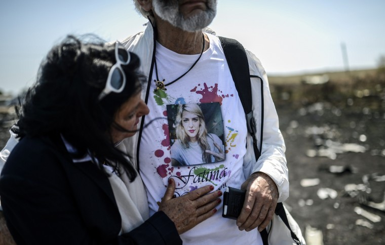 Angela Rudhart-Dyczynski and Jerzy Dyczynsk from Australia react as they arrive at the crash site of the Malaysia Airlines Flight MH17 to look for their late 25 years old daughter Fatima, near the village of Hrabove (Grabovo), in the Donetsk region. Ukraine sought on July 25 to avoid a political crisis after the shock resignation of its prime minister, as fighting between the army and rebels close to the Malaysian airliner crash site claimed over a dozen more lives. Dutch and Australian forces were being readied on July 26 for possible deployment to secure the rebel-held crash site of the Malaysia Airlines flight MH17 in east Ukraine where many victims' remains still lie nine days after the disaster claimed 298 lives. (Bulent Kilic/AFP-Getty Images)