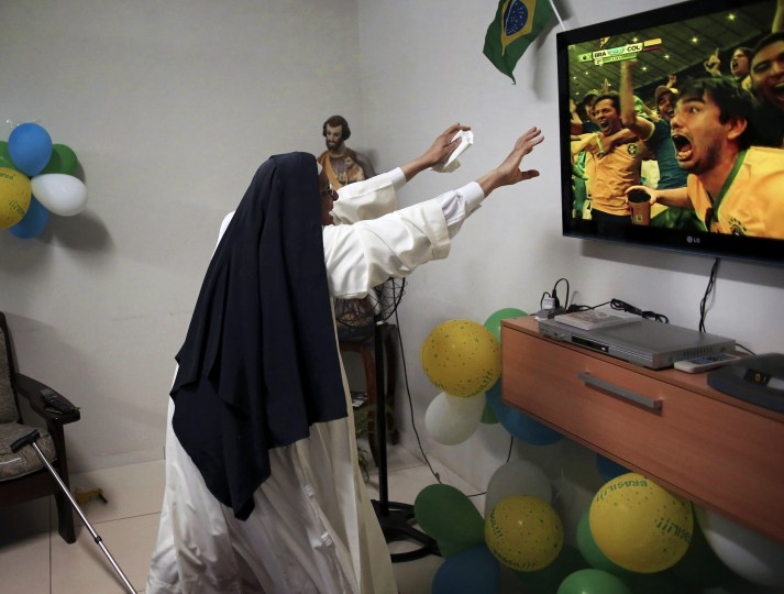 A nun from the enclosed monastery of Imaculada Conceicao celebrates a goal by Brazil during the 2014 World Cup quarter-final soccer match between Brazil and Colombia in Piratininga, in the state of Sao Paulo. (Nacho Doce/Reuters)