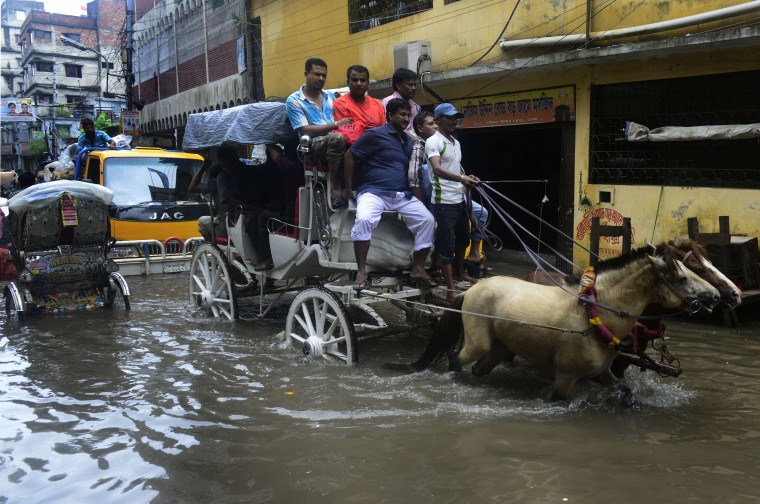A Bangladeshi driver guides his horse-cart through flood waters in old Dhaka. Seasonal monsoon rains brought Dhaka to a standstill, with vehicles scarce on the flooded roads, offices off to a slow start and people trapped in homes as low-lying areas of the city were inundated. (Munir uz Zaman/Getty Images)