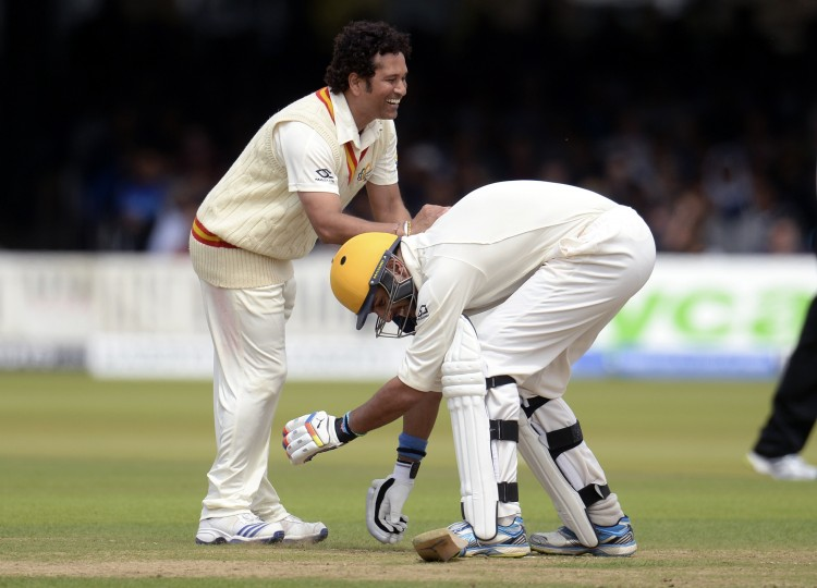 MCC's captain Sachin Tendulkar smiles as Rest of the World's Yuvraj Singh attempts to grab his leg during a cricket match to celebrate 200 years of Lord's at Lord's cricket ground in London. (Philip Brown/Reuters)