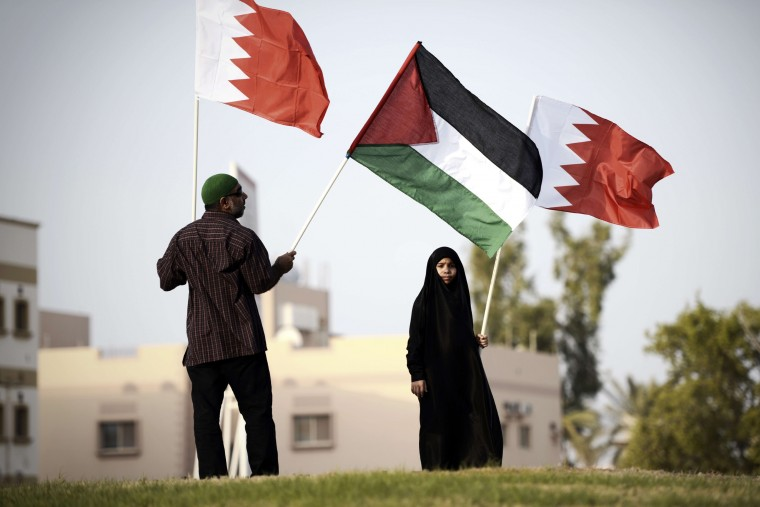 Bahrainis hold Palestinian flags during a protest against Israel's military operation in the Gaza Strip in the village of Karranah, west of Manama. Israel approved a four-hour extension of a temporary truce in Gaza, Israeli television said, after the Palestinian death toll topped 1,000 with the retrieval of more than 130 bodies. (Mohammed Al-Shaikh/AFP/Getty Images)