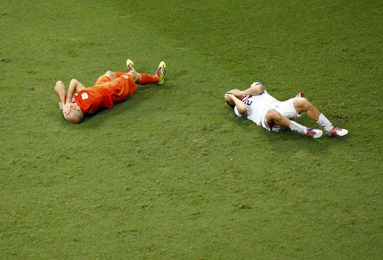 Arjen Robben of the Netherlands and Costa Rica's Johnny Acosta lie on the pitch after colliding with each other during extra time in their 2014 World Cup quarter-finals at the Fonte Nova arena in Salvador. Acosta was shown yellow card for the action. (Ruben Sprich/reuters)