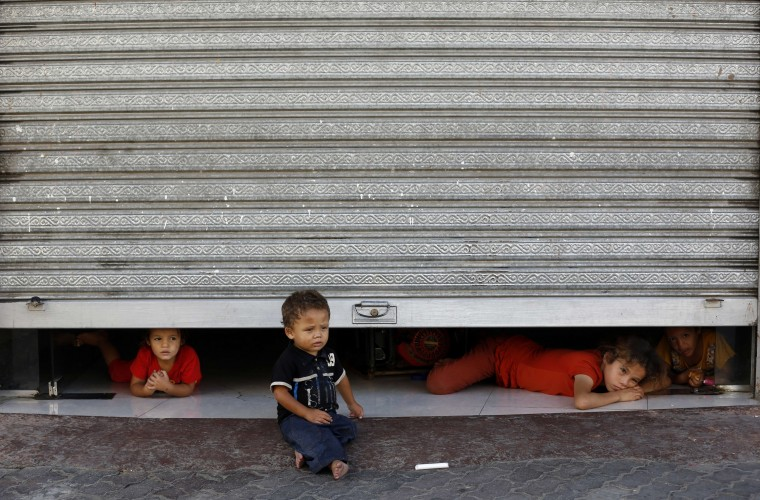 Displaced Palestinian children peak from under a shop door, where their family is taking shelter in Gaza City. Israel's security cabinet has approved a four-hour extension of a temporary truce in Gaza, prolonging an initial 12-hour ceasefire until midnight, Israeli television reported. (Mohammed Abed/AFP-Getty Images)