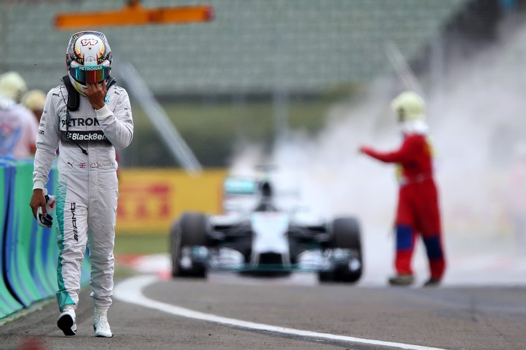 Lewis Hamilton of Great Britain and Mercedes GP walks away from his car after it caught fire during qualifying ahead of the Hungarian Formula One Grand Prix at Hungaroring in Budapest, Hungary. (Mark Thompson/Getty Images)