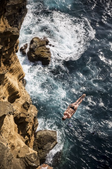 In this handout image provided by Red Bull, Gary Hunt of the UK dives from 27 metres off the cliff face of Islet Vila Franca do Campo during the fifth stop of the Red Bull Cliff Diving World Series, Azores, Portugal. (Romina Amato/Red Bull via Getty Images)