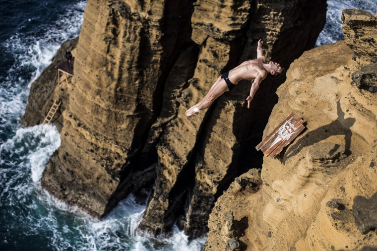 In this handout image provided by Red Bull, Steven LoBue of the USA dives from 27 metres off the cliff face of Islet Vila Franca do Campo during the fifth stop of the Red Bull Cliff Diving World Series, Azores, Portugal. (Dean Treml/Red Bull via Getty Images)