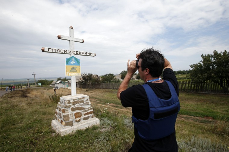 "An Organisation for Security and Cooperation in Europe (OSCE) monitor photographs the village sign at the crash site of Malaysia Airlines Flight MH17, near the settlement of Grabovo in the Donetsk region. International monitors said Saturday they had been allowed to visit more of the site where the Malaysian airliner crashed in rebel-held eastern Ukraine, though gunmen still stopped them approaching some of the wreckage. The words on the sign read, ""Save and Protect"" (top) and ""Grabovo"" (bottom). (Maxim Zmeyev/Reuters)"