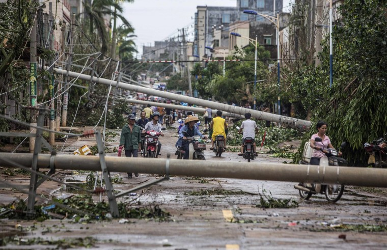 Residents travel on a street blocked by fallen electricity poles after Typhoon Rammasun hit Leizhou, Guangdong province. A super typhoon has killed at least fourteen people in China since making landfall on Friday afternoon, state media said on Saturday, after hitting parts of the Philippines and leaving 77 dead. (China Stringer Network/Reuters)