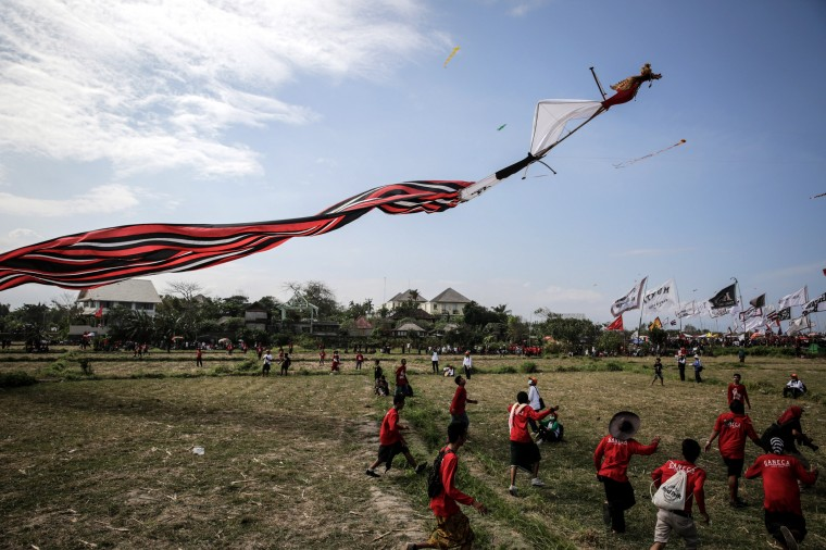 A traditional kite named Janggan is flown during the Bali Kite Festival in Denpasar, Bali, Indonesia. The event is a seasonal religious festival, which is intended to send a message to Hindu gods to create abundant harvests and crops. Approximately 1322 traditional kites are flown during the three day festival. (Agung Parameswara/Getty Images)