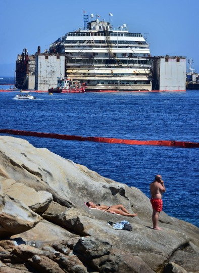 Sunbathers on the rocks at Giglio Island near the wreck of the Costa Concordia cruise ship. Italian salvage workers said today they would begin towing away the Costa Concordia on a final voyage to the scrapyard a day later than scheduled. The ship crashed off the island of Giglio in a nighttime disaster which left 32 people dead. The plan is to raise and tow away the 114,500-tonne vessel in an unprecedented and delicate operation for its final journey to the shipyard where it was built in the port of Genoa. (Giuseppe Cacace/AFP-Getty Images)