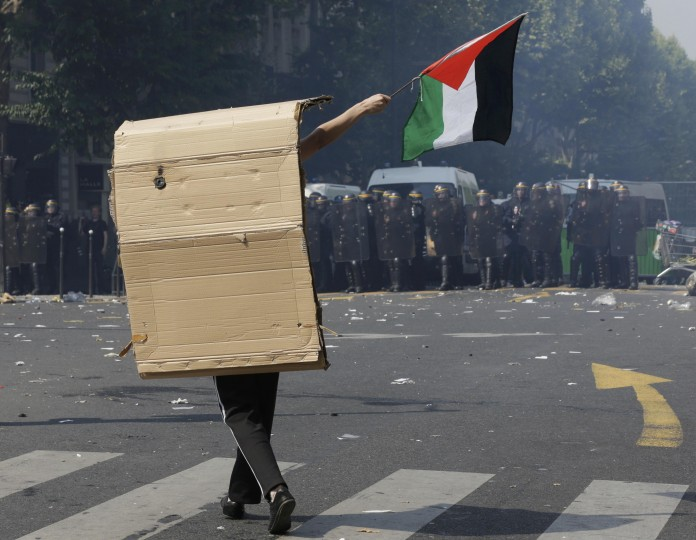A pro-Palestinian protester confronts riot police during during a demonstration against violence in the Gaza strip which had been banned by police in Paris. (Philippe Wojazer/Reuters)