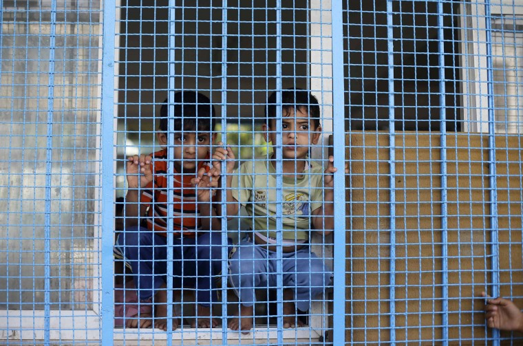Palestinian boys, who fled their family's house following an Israeli ground offensive, look out a classroom window as they stay at a United Nations-run school in Rafah in the southern Gaza Strip. Israeli forces on Saturday pressed ahead with a ground offensive in the Gaza Strip, where Palestinian militants kept firing rockets deep into Israel's heartland, pushing the death toll past 300 in almost two weeks of conflict. (Ibraheem Abu Mustafa/Reuters)