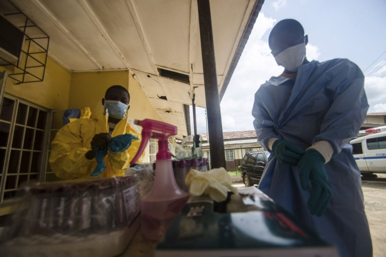 Medical staff put on protective gear in Kenema government hospital before taking a sample from a suspected Ebola patient in Kenema, July 10, 2014. (REUTERS/Tommy Trenchard)