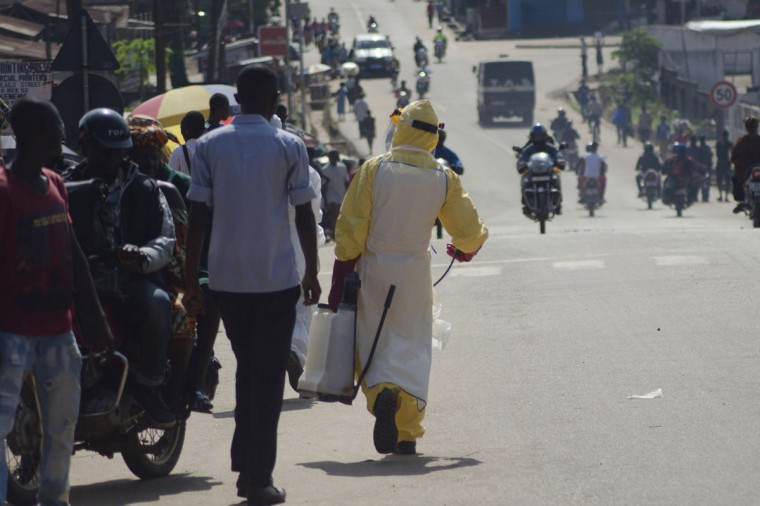 A health worker with disinfectant spray walks down a street outside the government hospital in Kenema, July 10, 2014. (REUTERS/Tommy Trenchard)