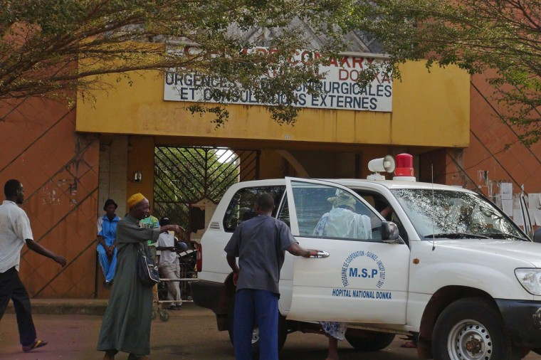 People walk in front of the entrance of the Donka Hospital, where victims of the ebola disease are being treated, in Conakry March 28, 2014. (REUTERS/Saliou Samb)
