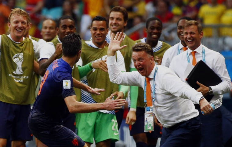 Robin van Persie of the Netherlands (front) celebrates his goal against Spain with coach Louis van Gaal during their 2014 World Cup Group B soccer match at the Fonte Nova arena in Salvador. (REUTERS/Michael Dalder)