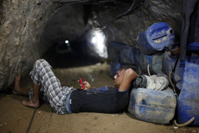 A Palestinian tunnel worker uses his mobile as he rests inside a smuggling tunnel beneath the Gaza-Egypt border in the southern Gaza Strip on July 19, 2013. (REUTERS/Ibraheem Abu Mustafa)