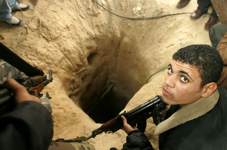 A Palestinian security officer prepares to seal a tunnel used to smuggle arms during an operation next to the border with Egypt at the Rafah refugee camp in the southern Gaza Strip on December11, 2005.