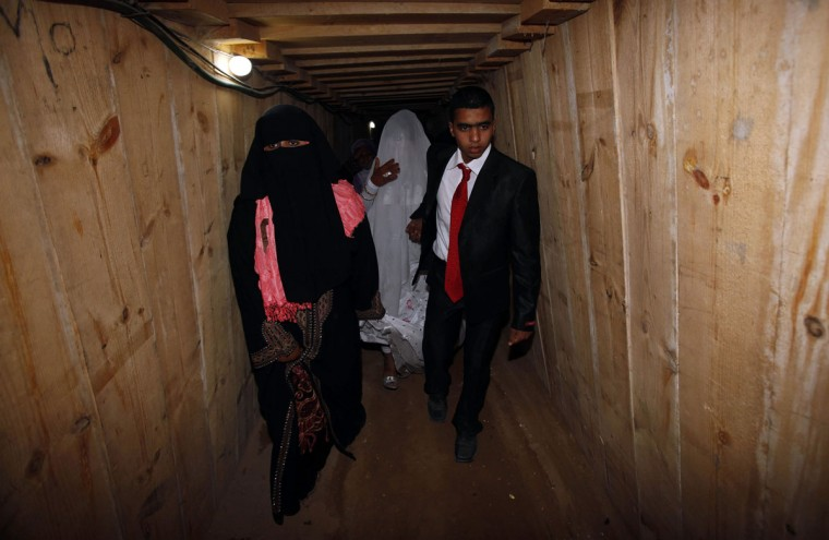Palestinian groom Emad al-Malalha, 21, walks with Manal Abu Shanar, 17, his Egyptian bride inside a smuggling tunnel beneath the Gaza-Egypt border in the southern Gaza Strip on March 21, 2013. (REUTERS/Ibraheem Abu Mustafa)