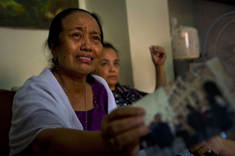 Grieving Indonesian Yuriah Tanzil (L), sister of Ninik Yuriani, a passenger of Malaysia Airlines flight MH17, shows a photograph of her sister at the family residence in Jakarta on July 18, 2014 after the plane crashed in Ukraine. All 298 people on board Flight MH17 en route to Kuala Lumpur from Amsterdam died when the plane crashed near a Ukrainian village, leaving a trail of carnage on the ground. At least 12 Indonesians were on board. (Romeo Gacad/AFP/Getty Images)