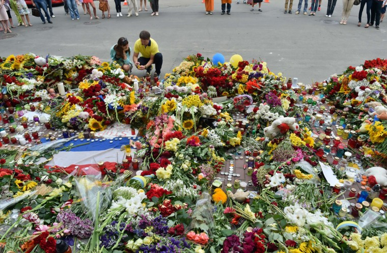 People lay flowers and light candles in front of the Embassy of the Netherlands in Kiev on July 18, 2014, a day after a Malaysian Airlines flight MH17 carrying 295 people from Amsterdam to Kuala Lumpur crashed in eastern Ukraine. Global demands mounted Friday to find those responsible for apparently shooting down th plane over rebel-held eastern Ukraine as relatives around the world mourned the deaths of the 298 people on board. (Sergei Supinsky/AFP/Getty Images)