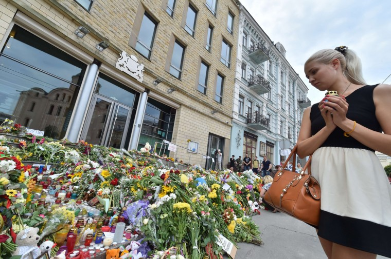 A girl holds candle as people lay flowers and light candles in front of the Embassy of the Netherlands in Kiev on July 18, 2014, to commemorate passengers of Malaysia Airlines flight MH17 carrying 295 people from Amsterdam to Kuala Lumpur which crashed in eastern Ukraine. Ukraine's prime minister said Friday that pro-Russian separatist rebels that Kiev believes shot down a Malaysian airliner with 298 people on board should face an international tribunal The Hague. (Sergei Supinsky/AFP/Getty Images)