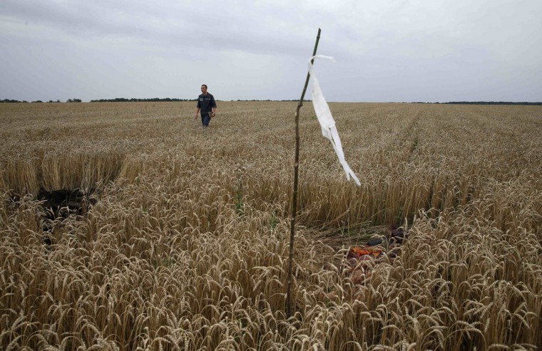 A member of the Ukrainian Emergency Ministry walks past a white flag marking the location of a body, as he searches for bodies close to the site of Thursday's Malaysia Airlines Boeing 777 plane crash near the settlement of Grabovo, in the Donetsk region July 18, 2014. World leaders demanded an international investigation into the shooting down of Malaysia Airlines Flight MH17 with 298 people on board over eastern Ukraine, as Kiev and Moscow blamed each other for a tragedy that stoked tensions between Russia and the West. (Maxim Zmeyev/Reuters)