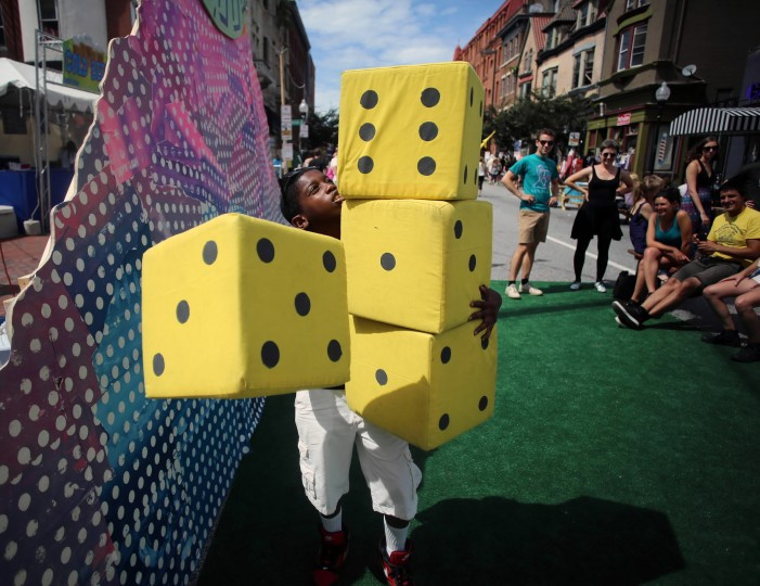 Anthony Fuller, 11, stacks oversized dice as he prepares to make a big roll playing Farkle, a dice game where the player tries to reach a certain dice combination marking a point value. He was plating the game on Charles Street at Artscape 2014. (Al Drago/Baltimor