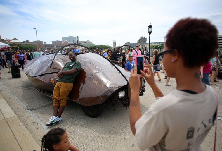 Brandon Hollinger, Baltimore, smiles for Adara Carter as he poses in front of the 'roach car' on display in the Art Cars area at Artscape 2014. The two work at The Loading Dock exhibit and were on their lunch. (Al Drago/Baltimore Sun)