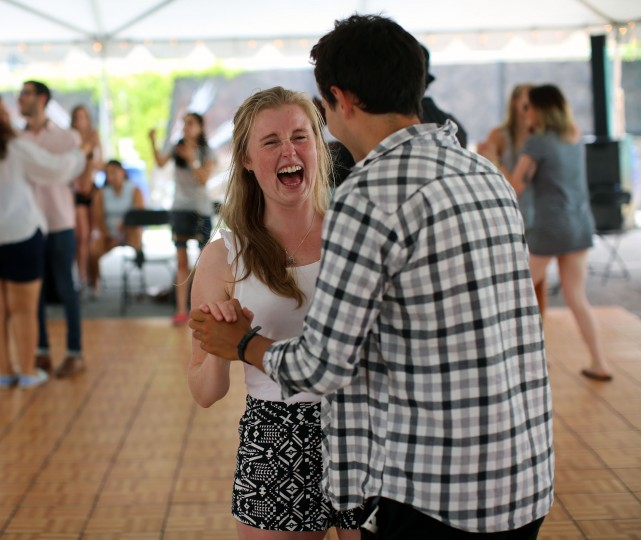 Hannah Hampton, of New Zealand, laughs while dancing with Jonathan Yamada, of Ireland, in the Arthur Murray Dance Studio tent on Charles Street at Artscape 2014. (Al Drago/Baltimore Sun)