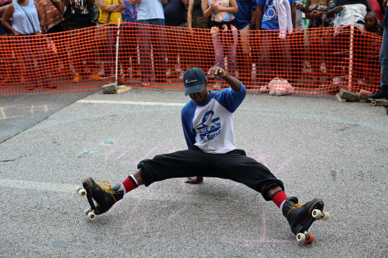 "Skater Mark Bank, also known as ""Swizzy,"" jumps back onto his skates while performing with It's My Skate Night at Artscape 2014. (Al Drago/Baltimore Sun)"