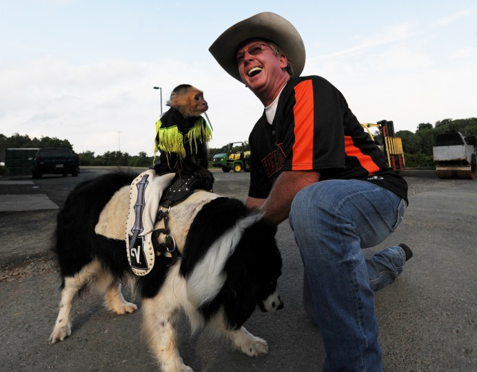 Tim Lepard, his monkey, Sam, and his dog, Bob, wait to be called out to throw the first pitch for the crowd at Ripken Stadium in Aberdeen before an Ironbirds game on Thursday, July 10, 2014. (Jon Sham/BSMG)