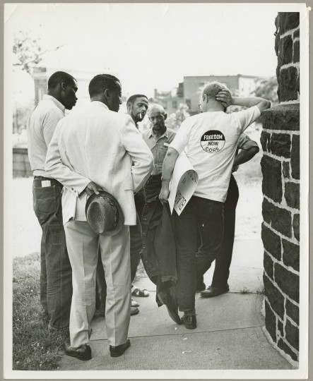 Baltimore Sun photographer Dick Childress finds members of Baltimore CORE smoking and chatting on a sidewalk, possibly during a demonstration. While we don't know the exact date and most of the men are not identified in this picture, the two men in the center are Walter Samuel Brooks (left), Baltimore CORE director, and Daniel Gant (right).