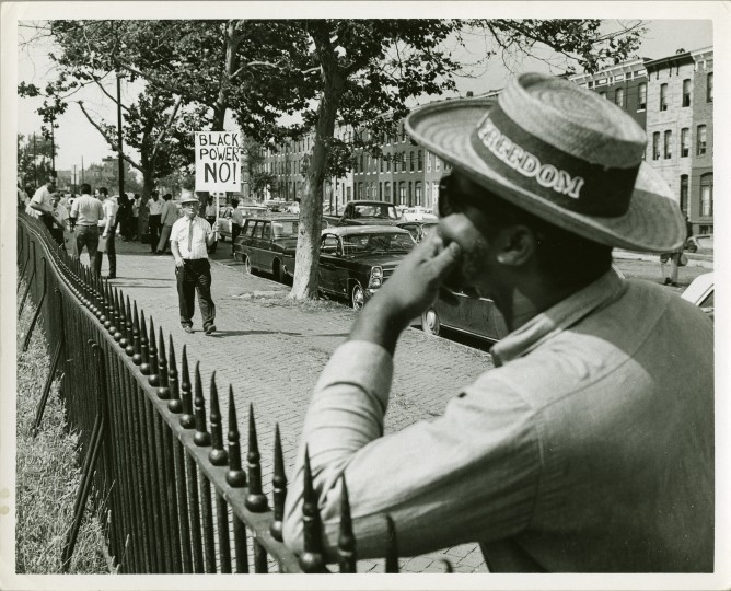 A CORE member watches infamous white supremacist and failed gubernatorial candidate Charles J. Luthardt protest a CORE event. (Richard Childress, Maryland Historical Society)Luthardt, a Glen Burnie resident, often visited the neighborhoods surrounding Patterson Park in his truck equipped with loudspeakers that he used to spout hate speech and play racist records, which he also sold. He was the chairman of the Fighting American Nationalists, but at these impromptu rallies his audience often consisted of Baltimore teenagers gathering around his truck. He believed the city was in the midst of a race war and in 1966 ran for governor on a platform of issuing guns to all white citizens at the state's expense.