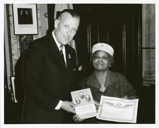 Mayor Theodore McKeldin awards Mrs. Jennie Gaines the first grant from the Baltimore Urban Renewal and Housing Authority. (Nat Lipsitz, January 14, 1966, Maryland Historical Society) Mrs. Jennie Gaines, homeowner, 515 North Carey Street (Harlem Park neighborhood) was the first person to receive a Federal Rehabilitation grant in the Mid-Atlantic region. Gaines was a 69-year-old widower who inherited her house from her mother and lived on Social Security. She used the grant to improve her home. McKeldin is seen delivering her award and holding a copy of his 1964 MdHS-published book, No Mean City.