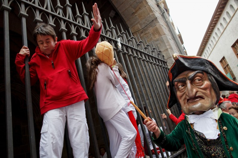 Caravinagre 'Vinegar face' kiliki hits children during the Comparsa de Gigantes y Cabezudos 'Giants and Big Heads parade' during the second day of the San Fermin Running Of The Bulls festival on July 7, 2014 in Pamplona, Spain. (Photo by Pablo Blazquez Dominguez/Getty Images)