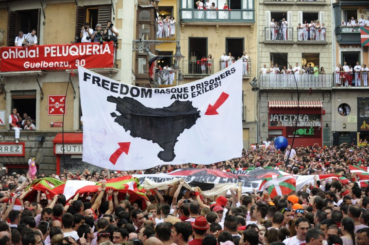 Participants hold flags of the Basque Country and a giant banner in support of Basque prisoners as they celebrate the 'Chupinazo' to mark the start at noon sharp of the San Fermin Festival on July 6, 2014 in front of the Town Hall of Pamplona, northern Spain. A red-and-white sea of revellers soaked each other with wine in a packed Pamplona square on Sunday to kick off Spain's most famous fiesta, the San Fermin bull-running festival. (ANDER GILLENEA/AFP/Getty Images)