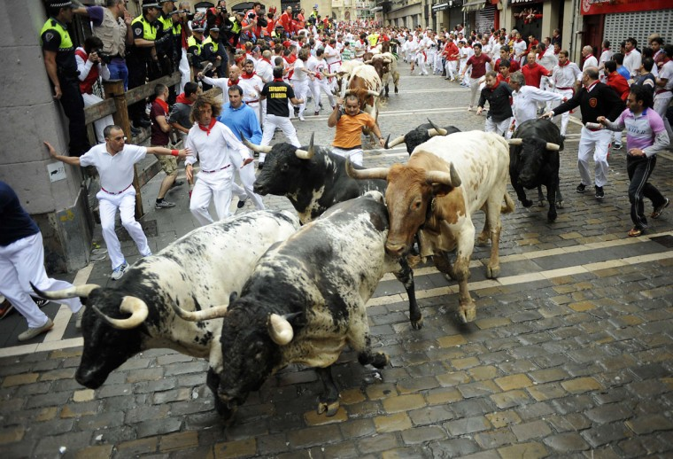 Participants run behind Torrestrella's bulls during the first bull-run of the San Fermin Festival, on July 7, 2014, in Pamplona, northern Spain. The festival is a symbol of Spanish culture that attracts thousands of tourists to watch the bull runs despite heavy condemnation from animal rights groups. (ANDER GILLENEA/AFP/Getty Images)