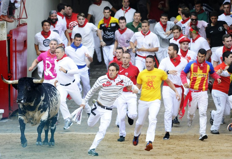 Participants run in front of Torrestrella's bulls during the first bull-run of the San Fermin Festival, on July 7, 2014, in Pamplona, northern Spain. (RAFA RIVAS/AFP/Getty Images)